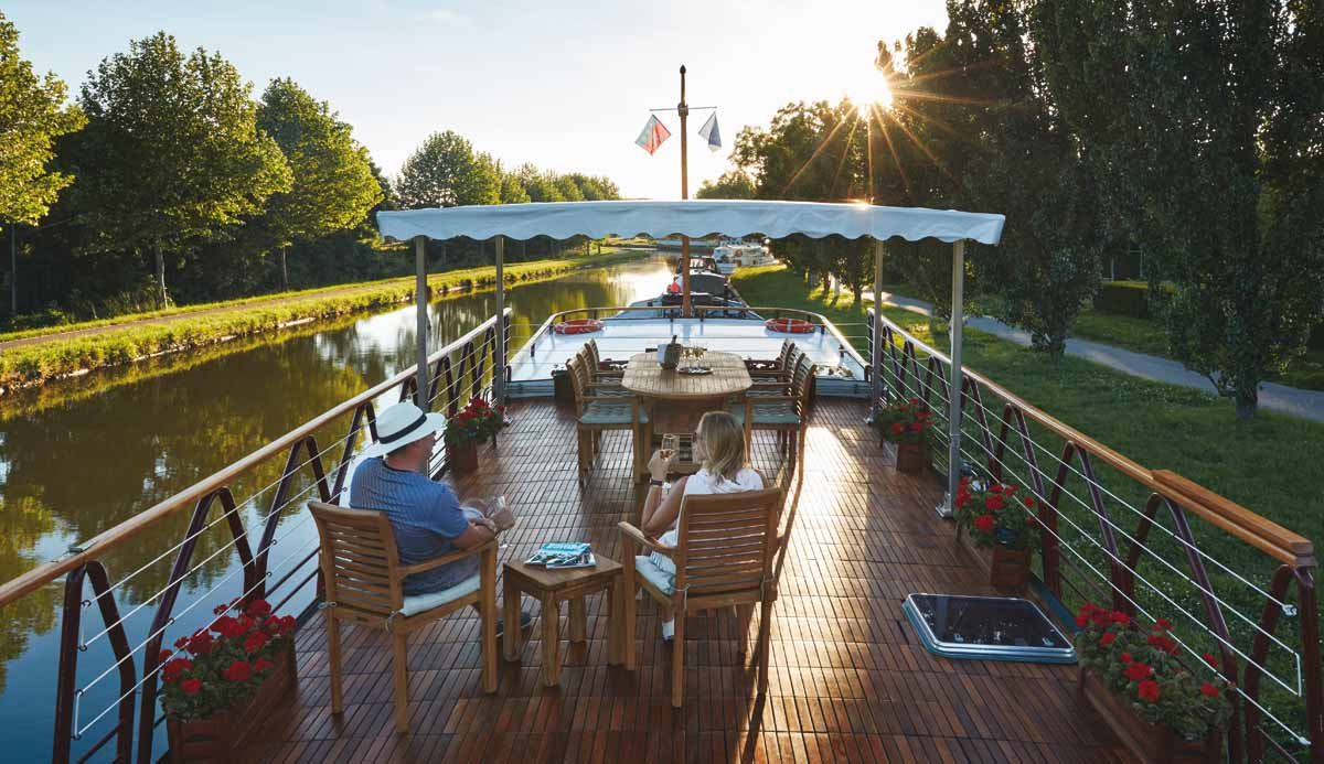 elderly couple relaxing on the top deck of a river cruise boat in france