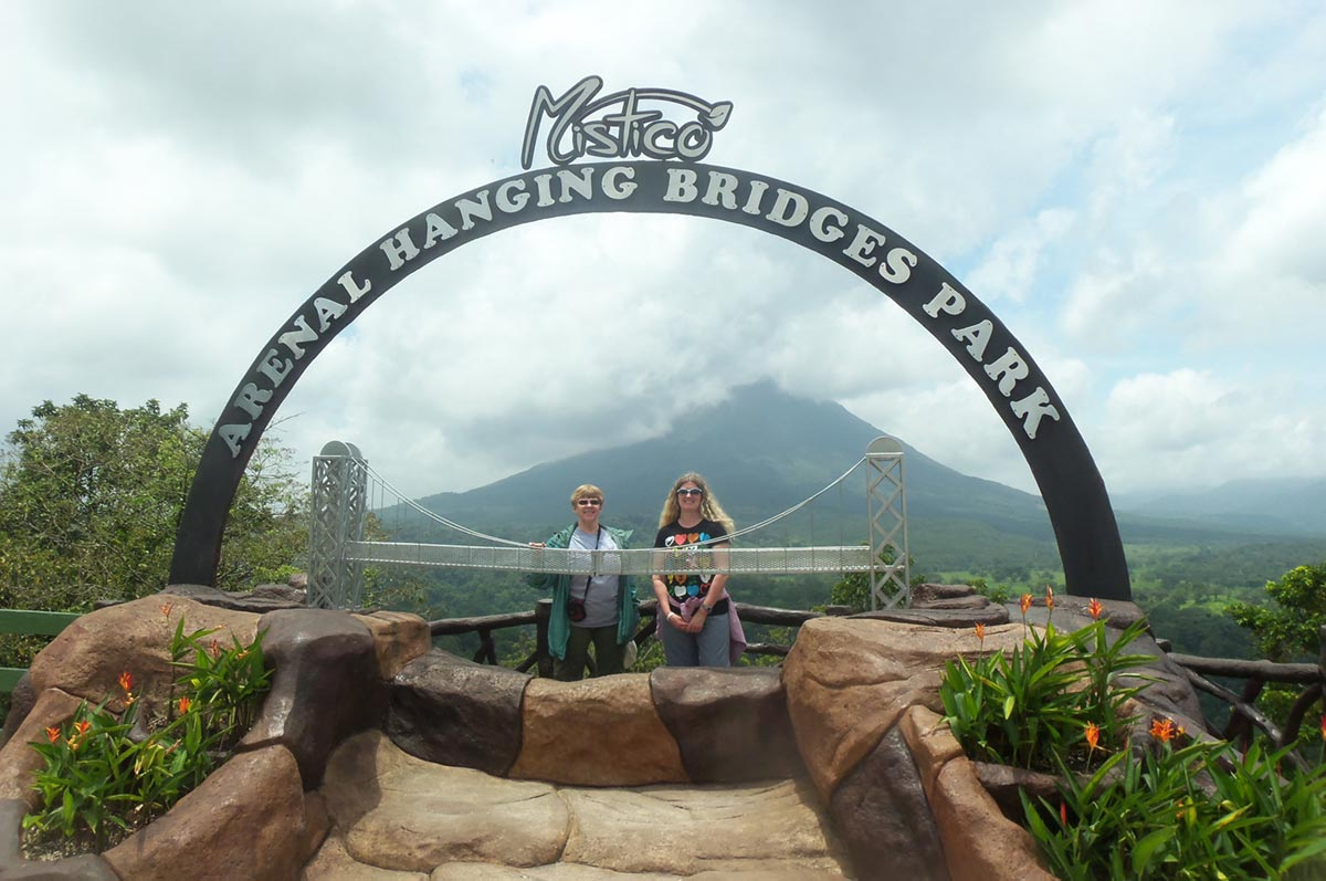 Julie Goergen and friend underneath the Mistico Arenal hanging bridges park arch