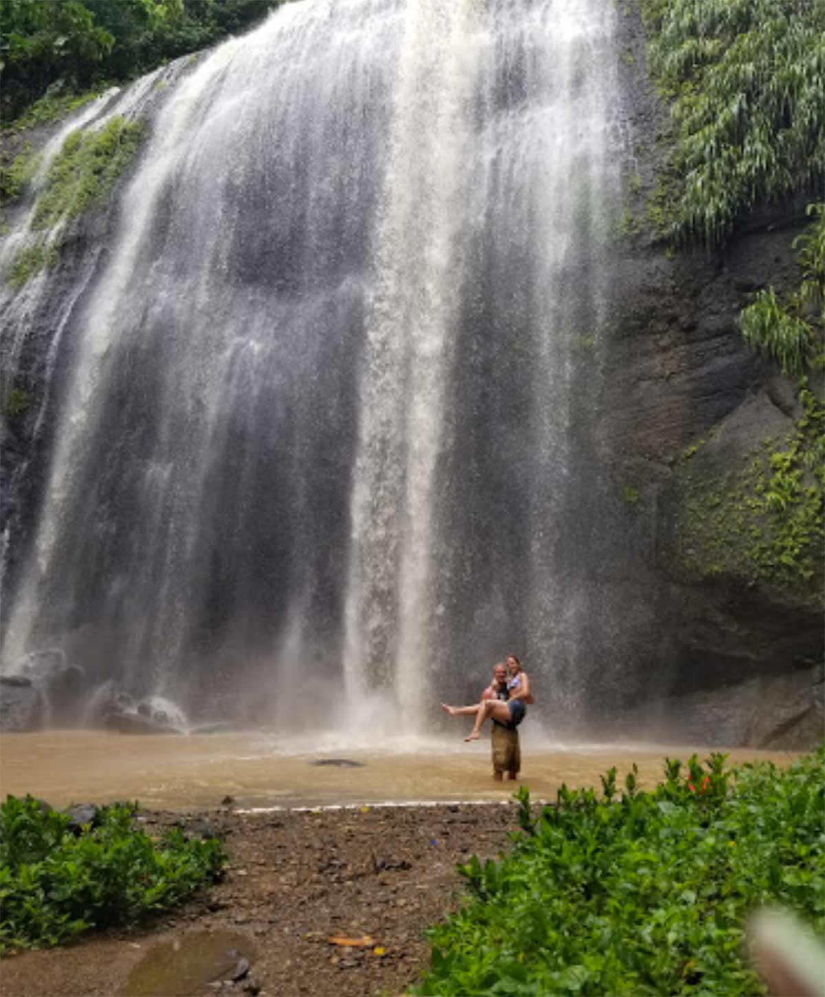Honeymoon couple standing under a waterfall in hawaii