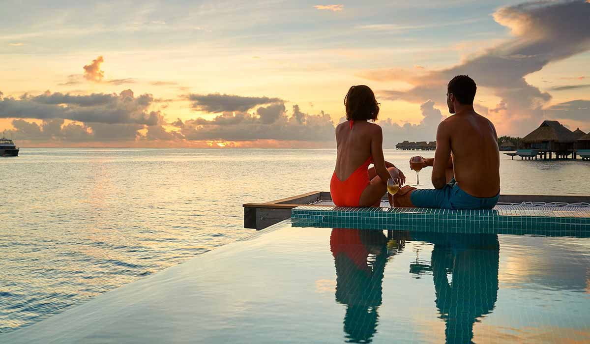 a couple sitting in the infiinity pool of their overwater bungalow in bora bora tahiti