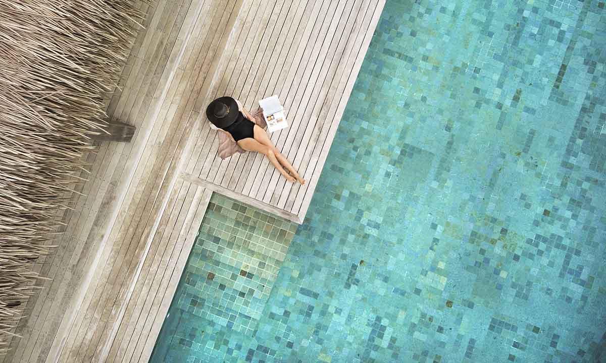 Six-Senses-Fiji woman reading a newspaper by the pool