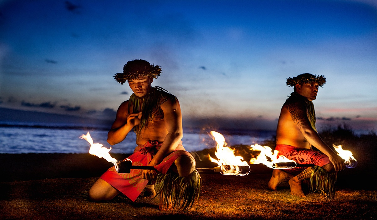 Hawaiian dancers fire dancing in front of blue sunset